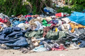 Pile of old clothes and shoes dumped on the grass